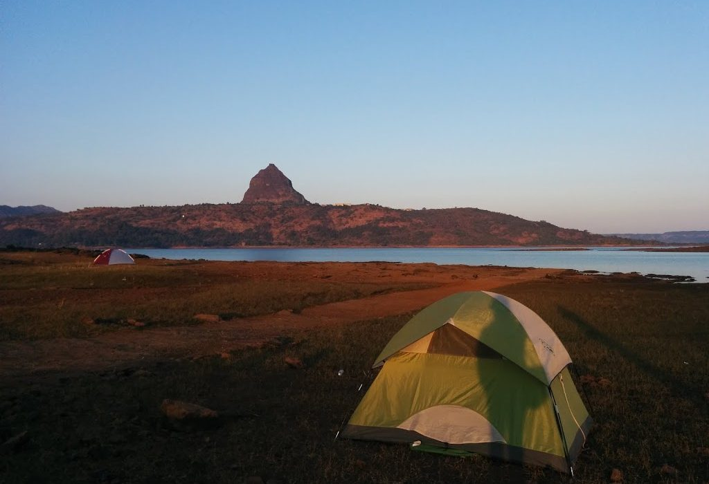 a tent against a lake and hillside